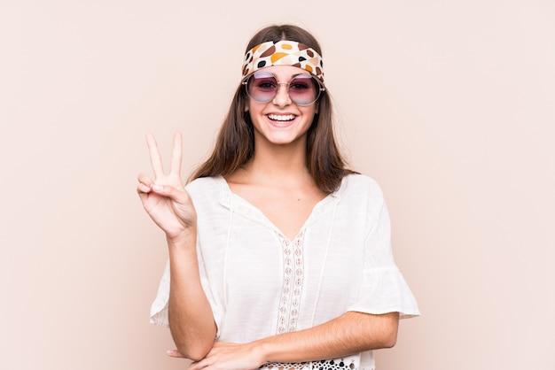 La giovane donna caucasica del hipter ha isolato la mostra del numero due con le dita.