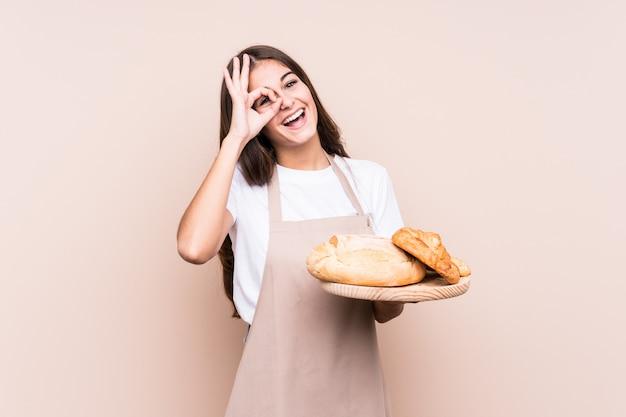 La giovane donna caucasica del panettiere ha isolato eccitato mantenendo il gesto giusto sull'occhio.