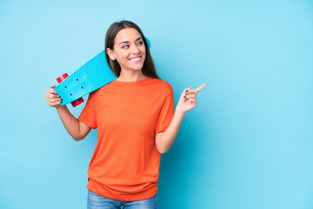 La giovane donna caucasica del pattinatore ha isolato sorridere e indicare da parte, mostrando qualcosa nello spazio.