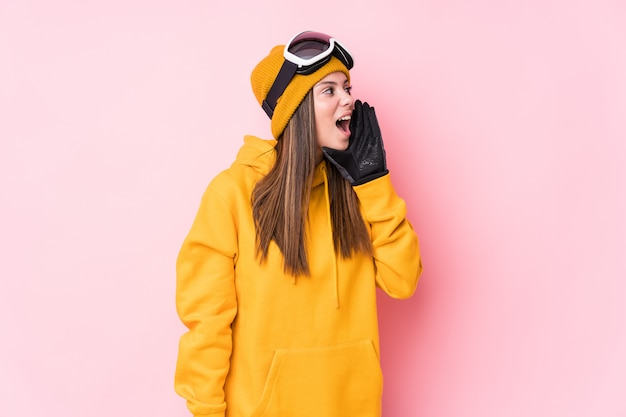 La giovane donna caucasica dello sciatore che grida e che tiene la palma vicino ha aperto la bocca.