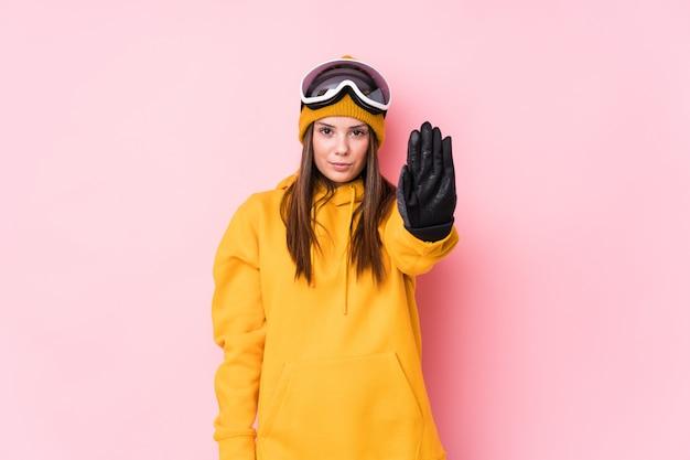 La giovane donna caucasica dello sciatore ha isolato la condizione con il fanale di arresto di rappresentazione della mano tesa, impedendovi.