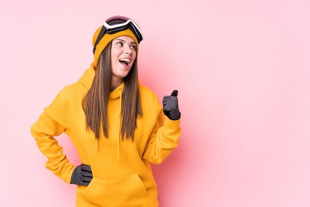 La giovane donna caucasica dello sciatore indica con il pollice via, ridendo e spensierato.