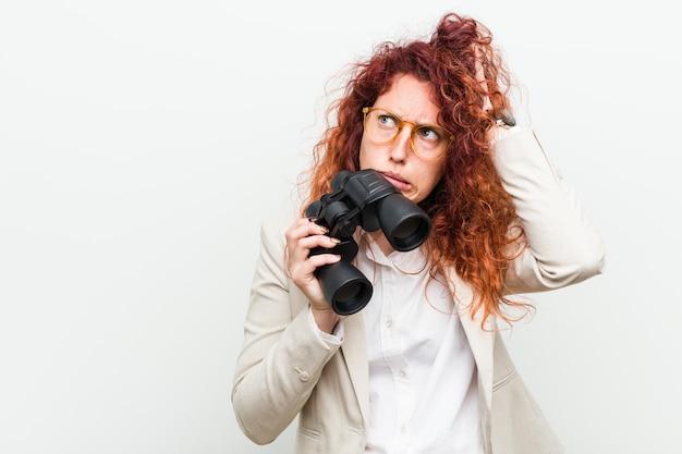 La giovane donna caucasica di affari di redhead che tiene un binocolo che è stata colpita, ha ricordato l'incontro importante.