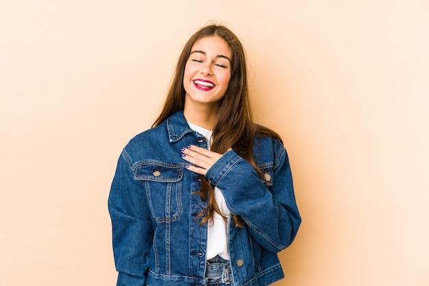 La giovane donna caucasica e la parete beige ride fragorosamente tenendo la mano sul petto.
