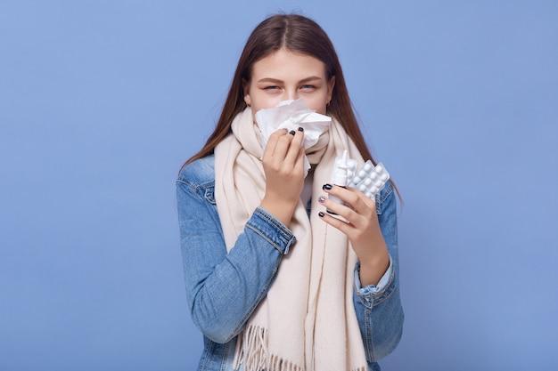 La giovane donna caucasica ha il raffreddore che cola e cola, tiene in mano pillole e spray nasale, indossa sciarpa calda e giacca di jeans