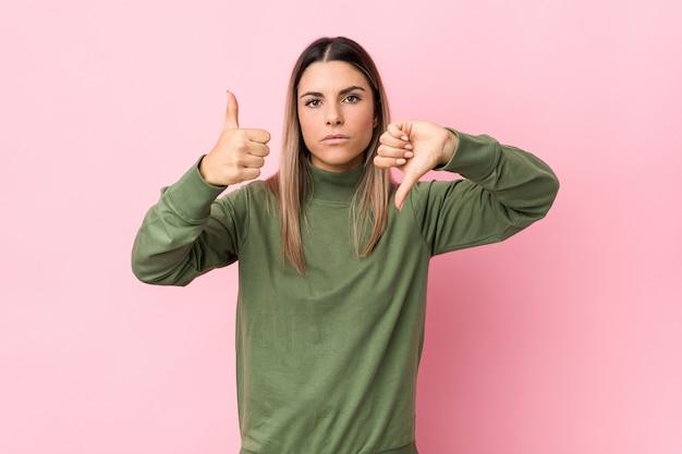 La giovane donna caucasica ha isolato la mostra dei pollici su e dei pollici giù, difficile sceglie il concetto