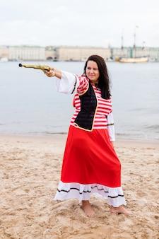 La giovane donna caucasica in costume da pirata rosso e bianco prende la mira con la pistola.