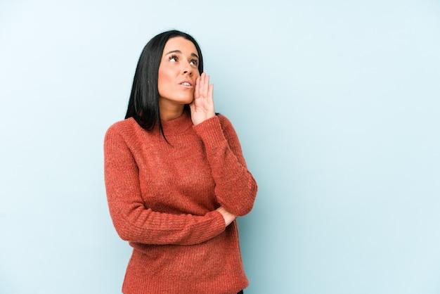 La giovane donna caucasica isolata su una parete blu sta dicendo una notizia di frenata calda segreta e sta guardando da parte