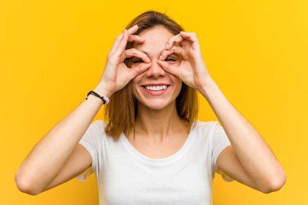 La giovane donna caucasica naturale che mostra l'approvazione firma sopra i suoi occhi