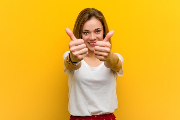 La giovane donna caucasica naturale con i pollici aumenta, incoraggia qualcosa, sostiene e rispetta il concetto.
