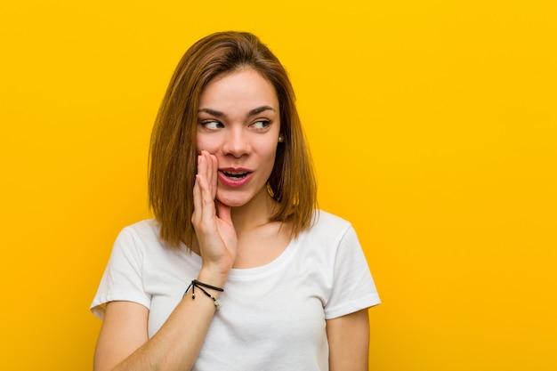 La giovane donna caucasica naturale sta dicendo una notizia di frenata calda segreta e sta guardando da parte