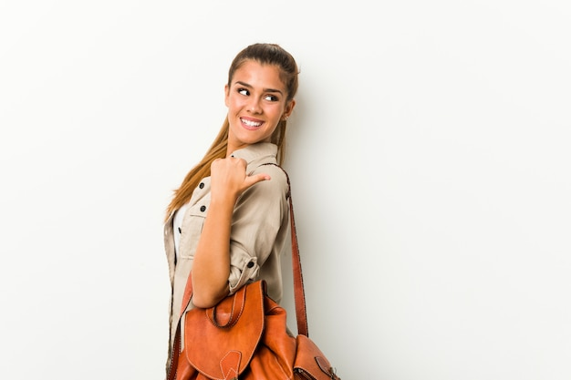 La giovane donna caucasica pronta per un viaggio indica con il dito di pollice via, ridendo e spensierata.