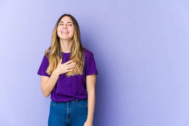La giovane donna caucasica ride ad alta voce tenendo la mano sul petto.