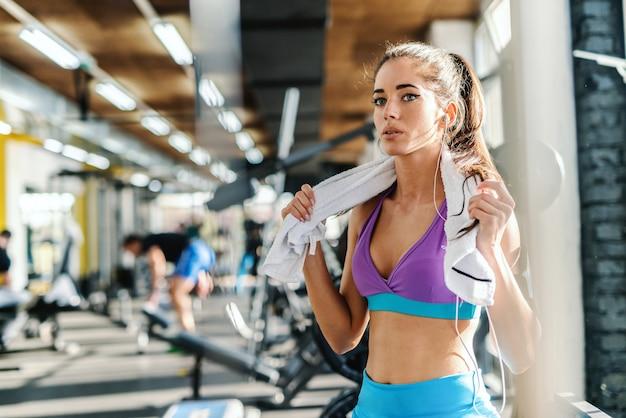 La giovane donna caucasica si è vestita in abbigliamento sportivo con l'asciugamano intorno al collo che si siede e che riposa dall'addestramento. interno della palestra.