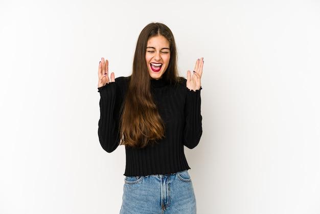 La giovane donna caucasica sulla parete bianca ride ad alta voce tenendo la mano sul petto.