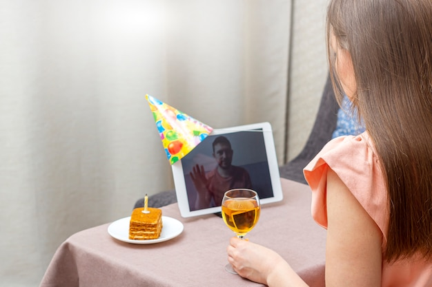 La giovane donna celebra il compleanno durante la quarantena. festa di compleanno virtuale online con la sua amica o amante. videochiamata su tablet.