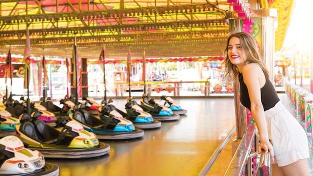 La giovane donna che esamina l'automobile di paraurti guida al parco di divertimenti