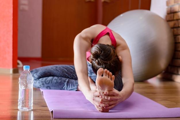 La giovane donna che fa l'allungamento si esercita delle gambe e della schiena su una stuoia porpora di forma fisica. il concetto di fitness a casa