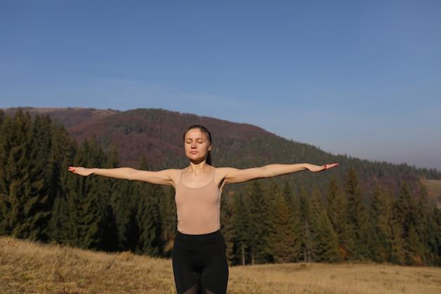 La giovane donna che fa l'allungamento si esercita sulla natura in montagne. posa di yoga di pratica della ragazza di sport in ghette. bellissimo paesaggio forestale