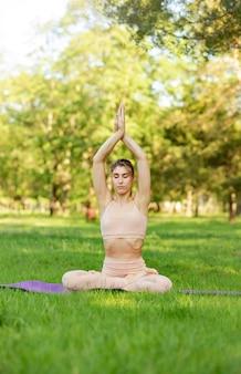 La giovane donna che fa l'esercizio di yoga e si rilassa nel parco di mattina all'estate