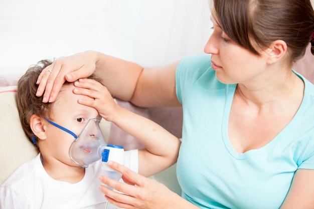 La giovane donna che fa l'inalazione con un figlio del nebulizzatore e tocca la sua fronte