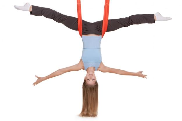 La giovane donna che fa l'yoga antigravità si esercita nell'allungamento dello spago
