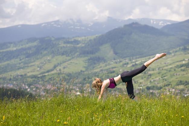 La giovane donna che fa l'yoga si esercita all'aperto.