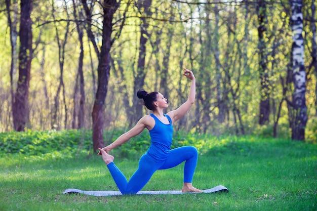 La giovane donna che fa l'yoga si esercita nel parco della città dell'estate