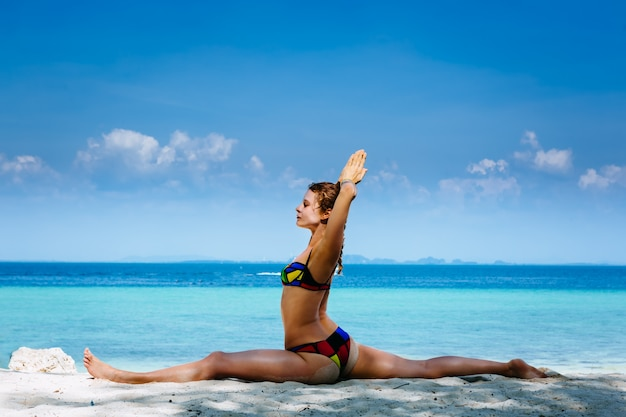 La giovane donna che fa l'yoga si esercita sulla spiaggia del mare