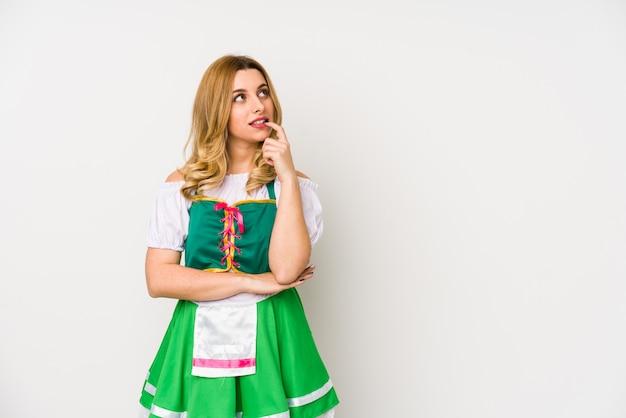 La giovane donna che indossa i vestiti di un giorno di san patrizio ha isolato il pensiero rilassato a qualcosa che esamina uno spazio della copia.