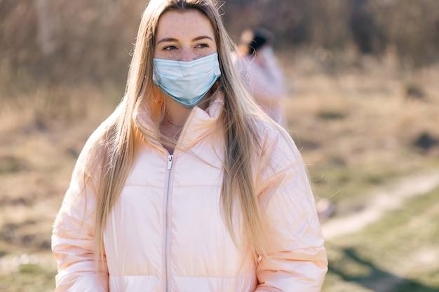 La giovane donna che indossa la maschera respiratoria protegge dal virus e dall'inquinamento