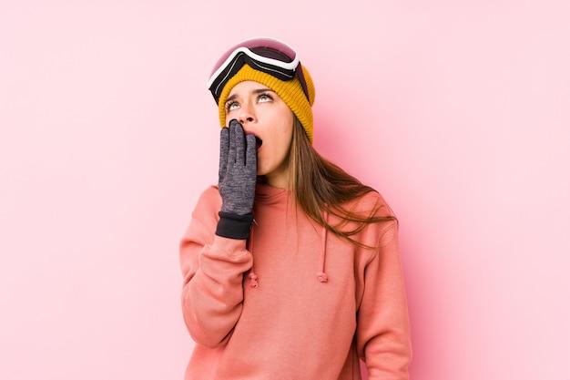 La giovane donna che indossa uno sci copre lo sbadiglio mostrando un gesto stanco che copre la bocca con la mano