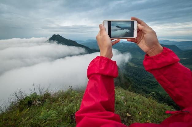 La giovane donna che per mezzo dello smart phone prende una foto mountain view