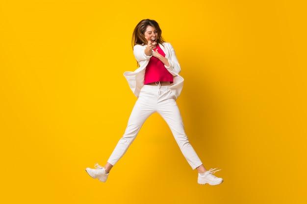 La giovane donna che salta sopra la parete gialla isolata che indica la parte anteriore