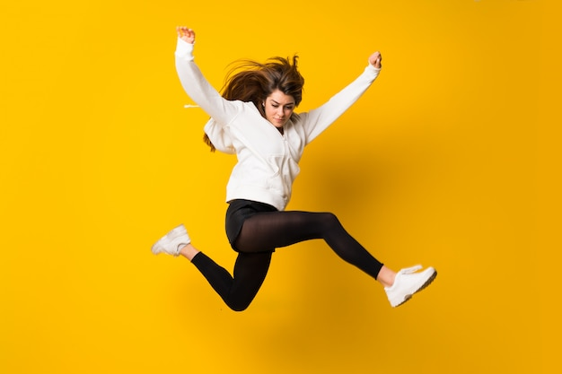 La giovane donna che salta sopra la parete gialla isolata