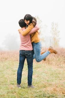 La giovane donna che salta sull'uomo con gioia in campagna