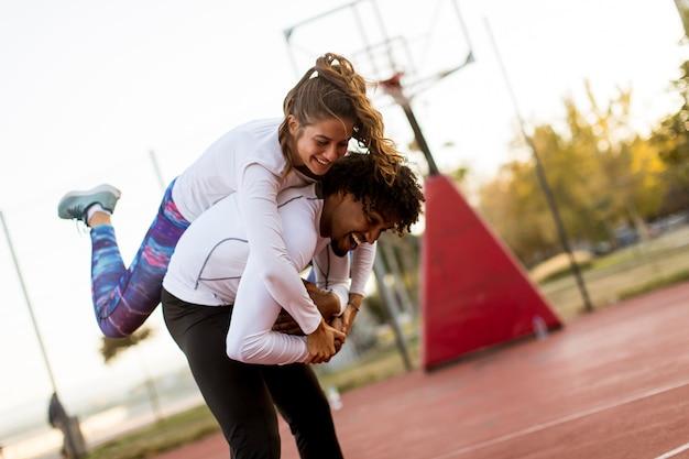 La giovane donna che salta sulle spalle degli uomini al campo da pallacanestro all'aperto