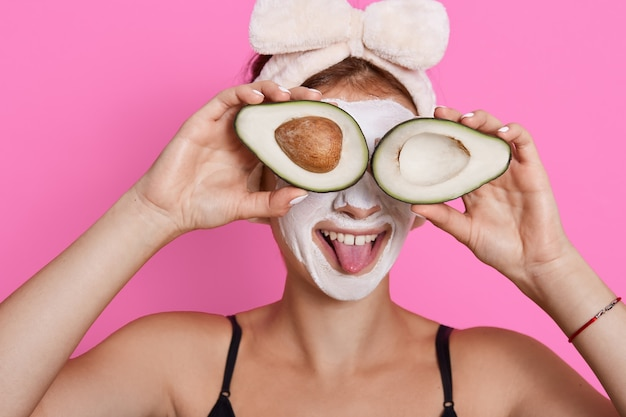La giovane donna che tiene due metà dell'avocado e che copre gli occhi con esso, mostrando la sua lingua, indossando la fascia per capelli, ha una maschera idratante sul viso, divertendosi mentre fa le procedure di bellezza a casa.