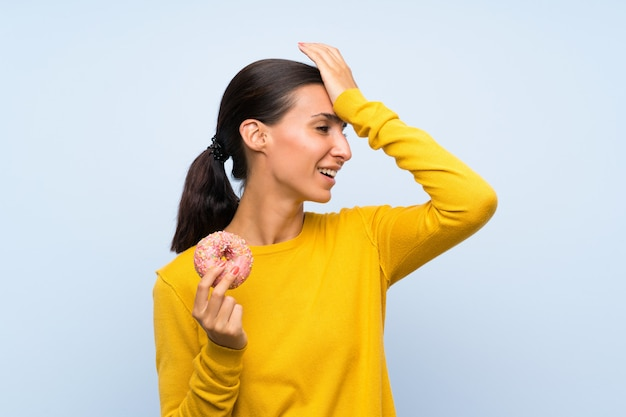 La giovane donna che tiene una ciambella sopra la parete blu isolata ha realizzato qualcosa e intendendo la soluzione