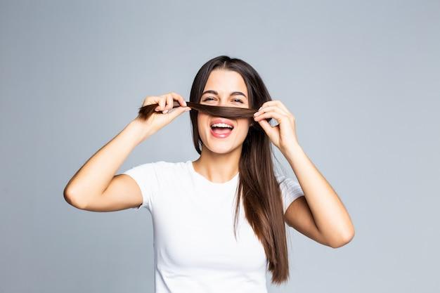 La giovane donna che tocca e gioca con i suoi capelli isolati su bianco
