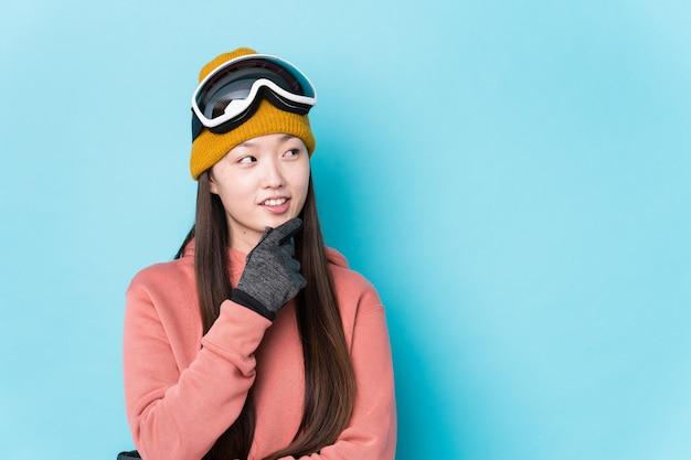 La giovane donna cinese che indossa i vestiti dello sci ha isolato il pensiero rilassato a qualcosa che esamina uno spazio della copia.