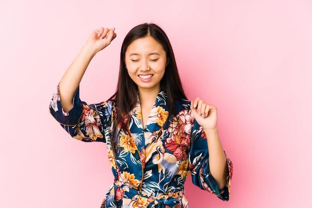 La giovane donna cinese che indossa un pigiama del kimono ha isolato la celebrazione di un giorno speciale, salta e alza le braccia con energia.