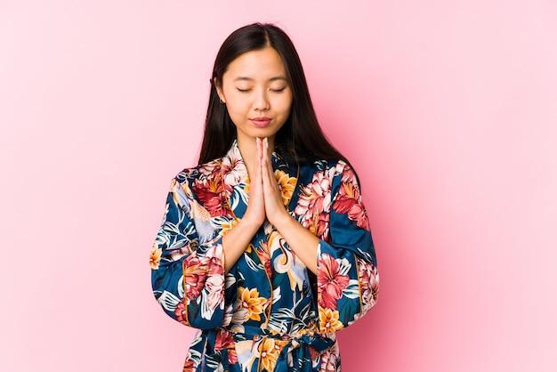 La giovane donna cinese che indossa un pigiama del kimono isolato tenendosi per mano dentro prega vicino alla bocca, si sente sicura.