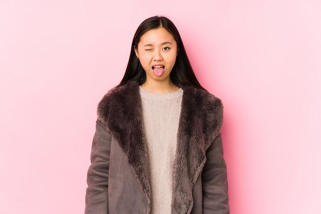La giovane donna cinese che porta un cappotto ha isolato la lingua attaccante divertente ed amichevole.