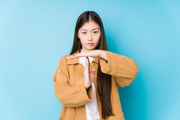 La giovane donna cinese che posa in una parete blu ha isolato la mostra del gesto di prespegnimento.