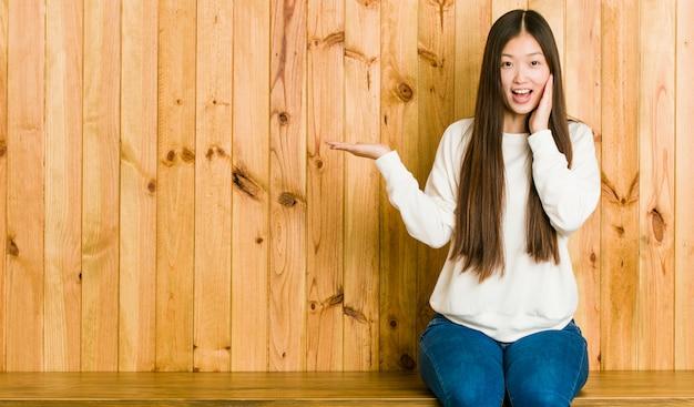 La giovane donna cinese che si siede su un posto di legno tiene lo spazio della copia su una palma, tiene la mano sulla guancia. stupito e felice.