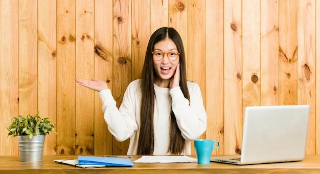 La giovane donna cinese che studia sul suo scrittorio e tiene consegna la guancia