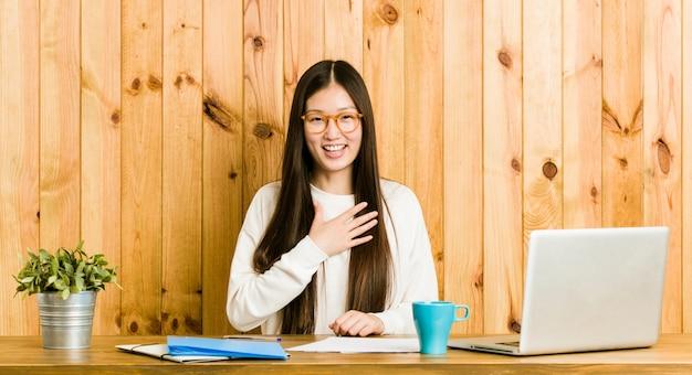 La giovane donna cinese che studia sulla sua scrivania ride ad alta voce tenendo la mano sul petto.