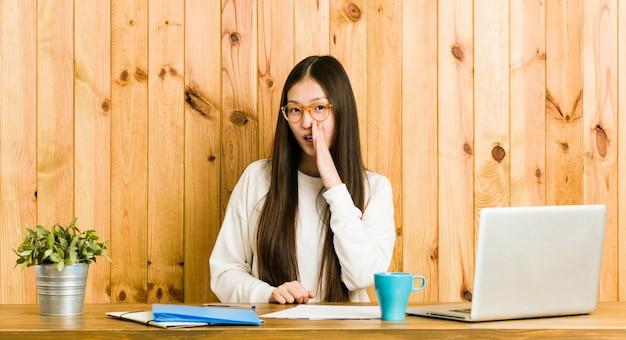 La giovane donna cinese che studia sulla sua scrivania sta dicendo una notizia di frenata calda segreta e sta guardando da parte
