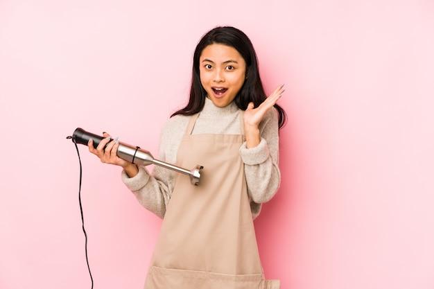 La giovane donna cinese che tiene un miscelatore ha isolato le grida molto arrabbiate e aggressive.